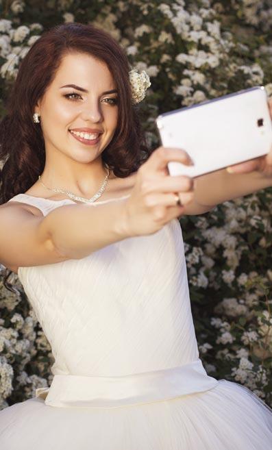 Bride taking a selfie in a wedding dress